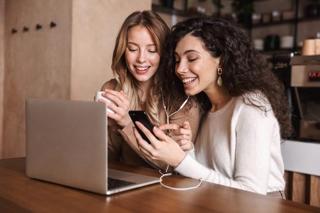 Dwie wesołe młode dziewczyny, które siedzą przy stoliku w kawiarni, bawią się razem, piją kawę, korzystają z laptopa, słuchają muzyki przez słuchawki i telefon komórkowy