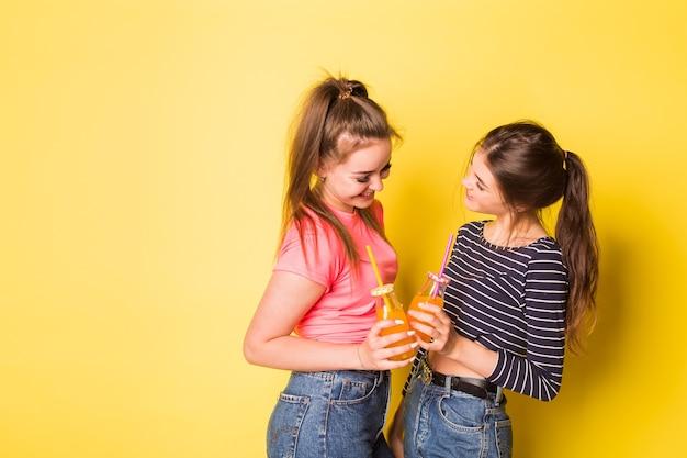 Dwie wesołe młode hipster naturalne piękno dziewczyny pozowanie razem na żółtym tle
