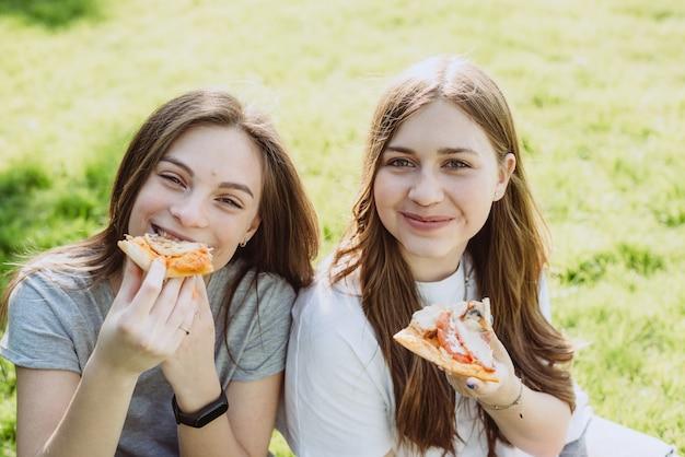 Dwie wesołe młode nastolatki przyjaciele w parku jedzenie pizzy. kobiety jedzą fast foody. nie zdrowa dieta. miękka selektywna ostrość.