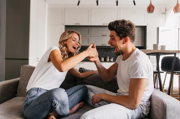 Dwie wesołe osoby siedzące na kanapie i grające na kciukach. mężczyzna wygląda na zaskoczonego, a jego dziewczyna wygląda na bardzo szczęśliwą i gotową do zwycięstwa.