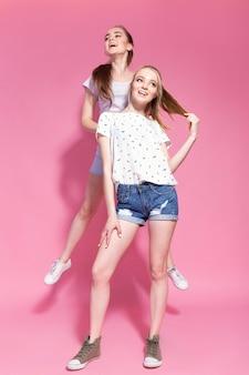 Dwie wesołe podekscytowane młode kobiety, skaczące i bawiące się razem.