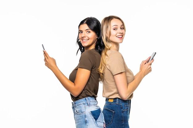 Dwie wesołe podekscytowane młode kobiety używają smartfonów i krzyczą nad białą ścianą