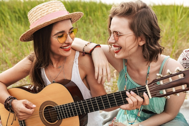 Dwie wesołe przyjaciółki relaksujące się na świeżym powietrzu, grające na gitarze