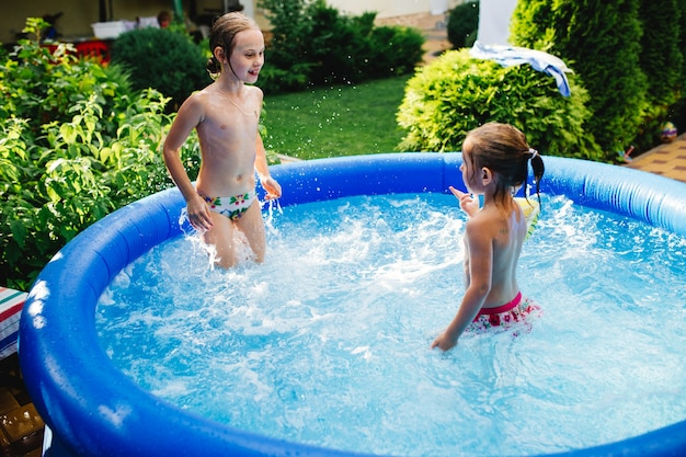 Dwie wesołe śliczne małe siostry grające i bawiące się, pluskanie i skakanie w nadmuchiwanym basenie na podwórku.
