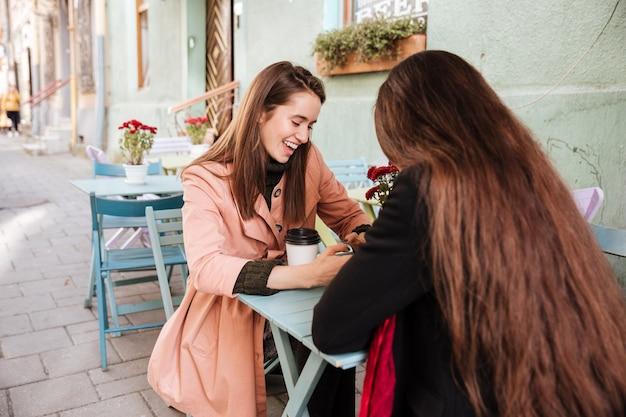 Dwie wesołe słodkie młode kobiety pijące kawę i śmiejące się w kawiarni na świeżym powietrzu