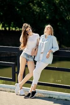 Dwie wesołe studentki stojąc na moście w gorący słoneczny dzień