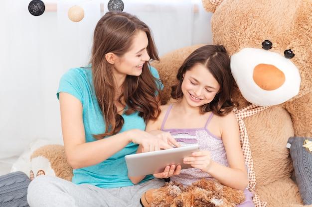 Dwie wesołe urocze siostry siedzące i używające tabletu razem w domu