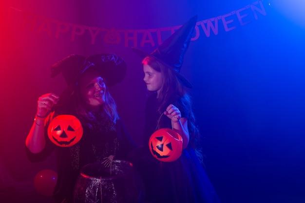 Dwie wiedźmy halloween robią miksturę i czarują w noc halloween. magia, święta i mistyczna koncepcja.