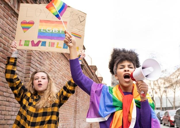 Dwie wieloetniczne kobiety świętujące dumę gejowską noszące tęczową flagę z symbolem lgbt