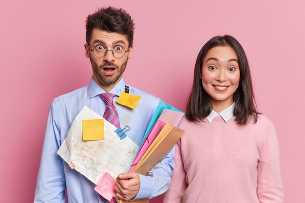 Dwie wieloetniczne koleżanki i koledzy spotykają się w biurze w celu stworzenia prezentacji, niosą dokumenty i naklejki z informacjami, przygotowując się do warsztatów lub wspólnych kursów. młodzi koledzy z klasy