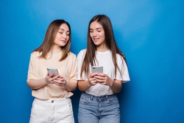 Dwie wieloetniczne letnie kobiety ubrane w wyrażające podekscytowanie lub zaskoczenie, podczas gdy obie używają telefonów komórkowych na niebieskiej ścianie