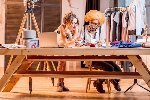 Dwie wieloetniczne projektantki mody pracujące w biurze z różnymi narzędziami krawieckimi i ubraniami