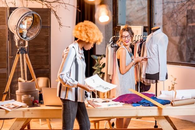 Dwie wieloetniczne projektantki mody pracujące z rysunkami ubrań stojących w biurze z różnymi narzędziami krawieckimi i manekinem