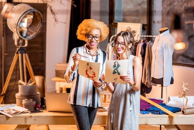 Dwie wieloetniczne projektantki mody pracujące z rysunkami ubrań stojących w pięknym biurze z różnymi narzędziami krawieckimi i ubraniami