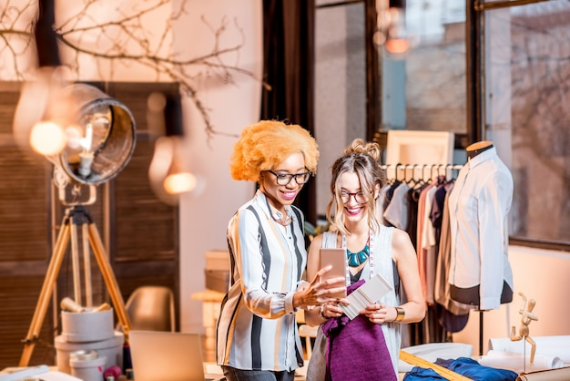 Dwie wieloetniczne projektantki mody pracujące ze smartfonem stojącym w biurze z różnymi narzędziami krawieckimi i ubraniami