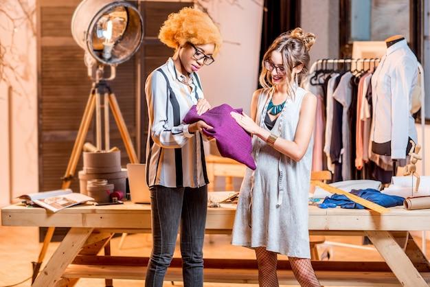 Dwie wieloetniczne projektantki mody wybierają tkaniny w biurze z różnymi narzędziami krawieckimi i ubraniami