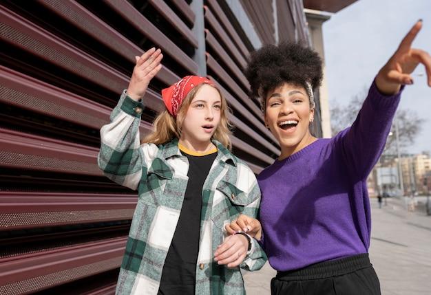 Dwie wielorasowe kobiety w mieście wskazują na coś