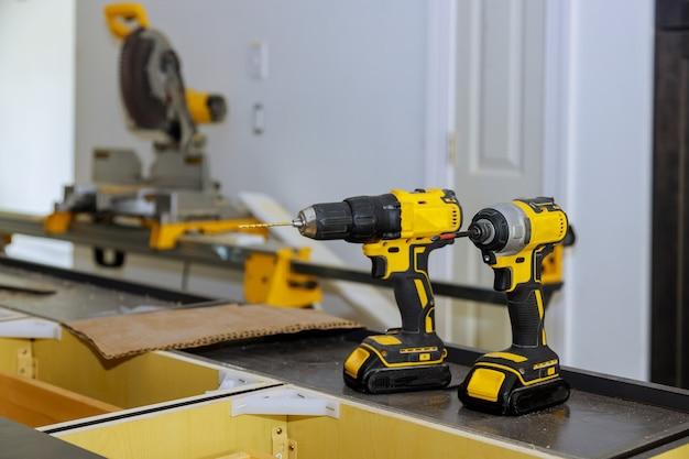 Dwie wiertarko-wkrętarki akumulatorowe z wiertłami, działające również jako wkrętarki na przyrządzie wiertarskim, profesjonalne narzędzie do obróbki drewna