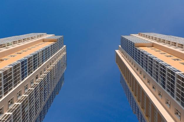 Dwie wieże. fasady nowych dwóch wysokich budynków błękitnego nieba, widok z dołu. przemysł budowlany