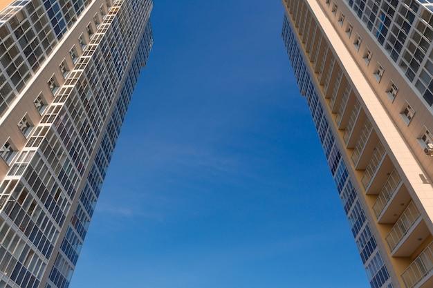Dwie wieże fasady nowych dwóch wysokich budynków na tle nieba widok z dołu przemysł budowlany