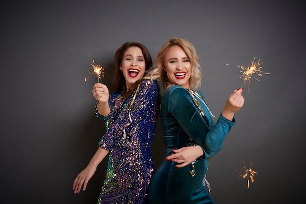 Dwie wspaniałe kobiety bawią się zimnymi ogniami