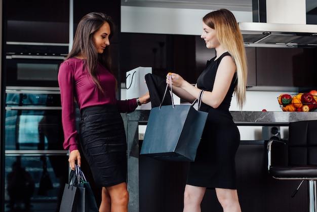 Dwie wspaniałe kobiety po zakupach w domu. dziewczyna pokazuje swoje zakupy koleżance stojącej w domu.