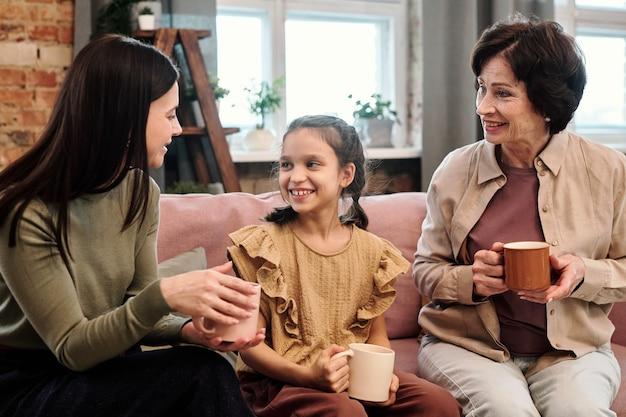 Dwie współczesne szczęśliwe kobiety w casualwear i urocza dziewczynka z gorącymi napojami siedząca na kanapie w salonie i prowadząca dyskusję