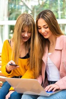 Dwie wyraziste młode kobiety używają telefonu komórkowego i laptopa