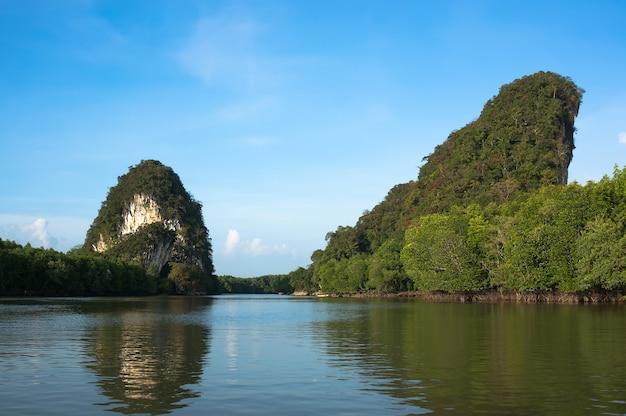 Dwie wysokie skały są główną atrakcją krabi tajlandii. rzeka między dwoma wysokimi klifami.