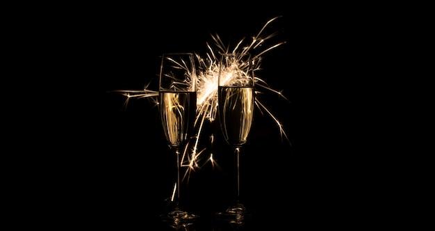 Dwie wysokie szklanki szampana w jasnych iskrach