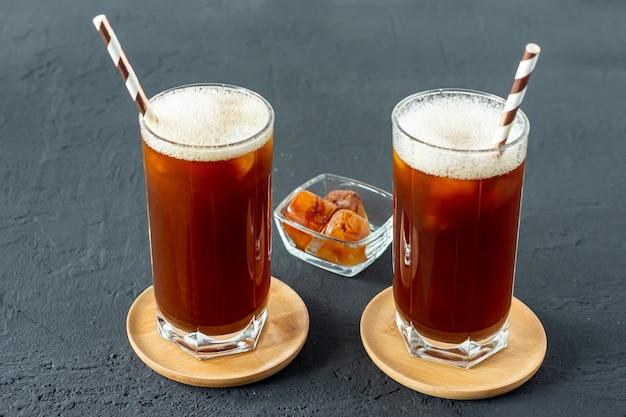 Dwie wysokie szklanki z mrożoną kawą na szarym tle, letnie orzeźwienie.
