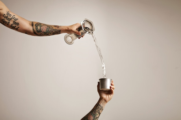 Dwie wytatuowane dłonie wylewające wodę z przezroczystego plastikowego aeropressu do małego stalowego kubka podróżnego na białym tle reklama alternatywnego parzenia kawy