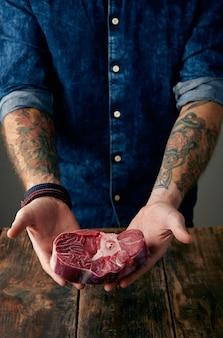Dwie wytatuowane ręce delikatnie trzymają stek mięsny nad starym drewnianym stołem. poruszaj się po aparacie.