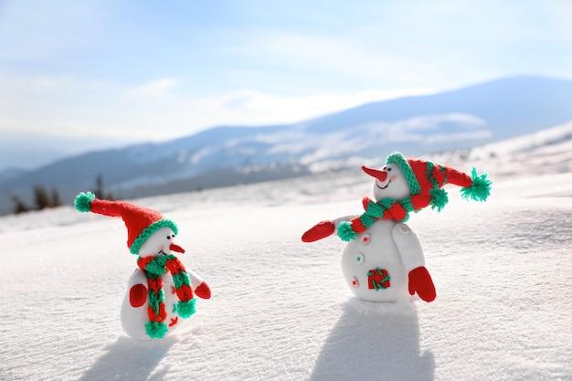 Dwie zabawki bałwanki w górskim kurorcie w słoneczny mroźny dzień. ferie zimowe