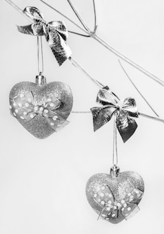 Dwie zabawki świąteczne srebrne błyszczące serca na gałązkach alternatywnej choinki wykonanej z suchego drewna pomalowanego na srebrno.