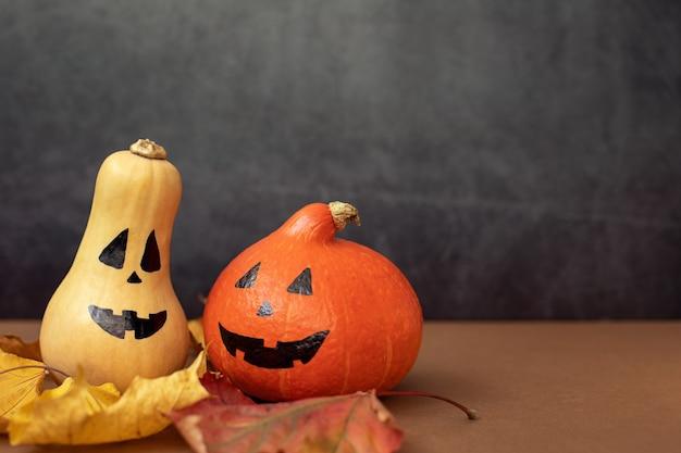 Dwie zabawne dynie halloween z pomalowanymi twarzami ciemnoszare tło koncepcja imprezy tematycznej
