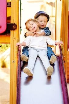 Dwie zabawne dzieci na zjeżdżalni na placu zabaw