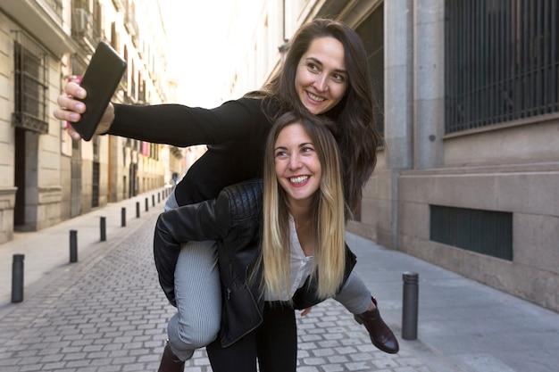 Dwie zabawne dziewczyny robiące selfie na ulicy miasta.
