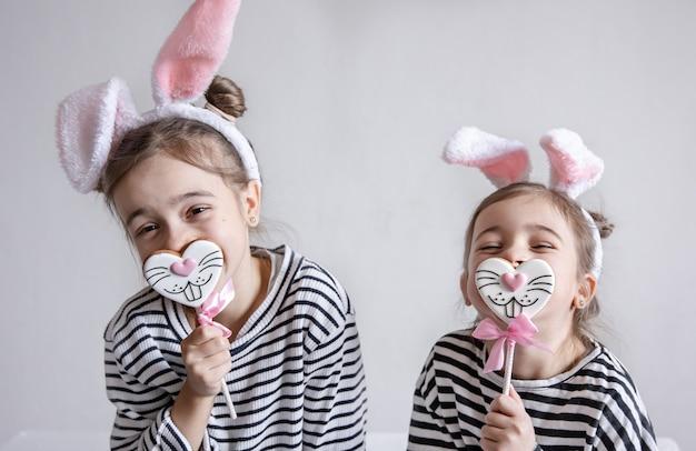 Dwie zabawne siostrzyczki pozują z wielkanocnymi pierniczkami w postaci buzi króliczków.