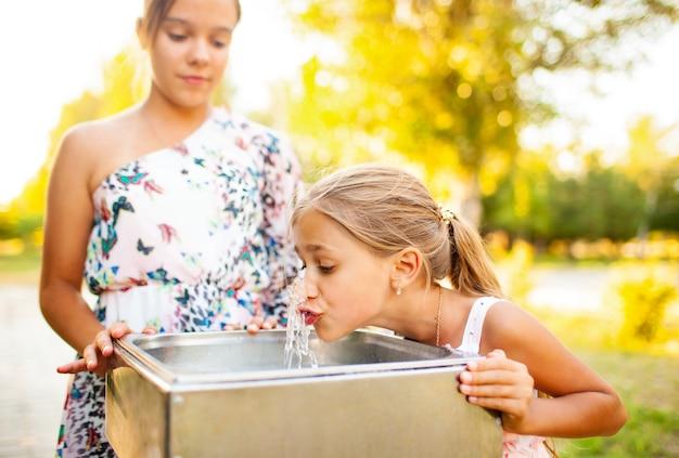 Dwie zabawne, wesołe, cudowne siostry piją chłodną, świeżą wodę z małej fontanny w ciepłym letnim słonecznym parku podczas długo oczekiwanych wakacji