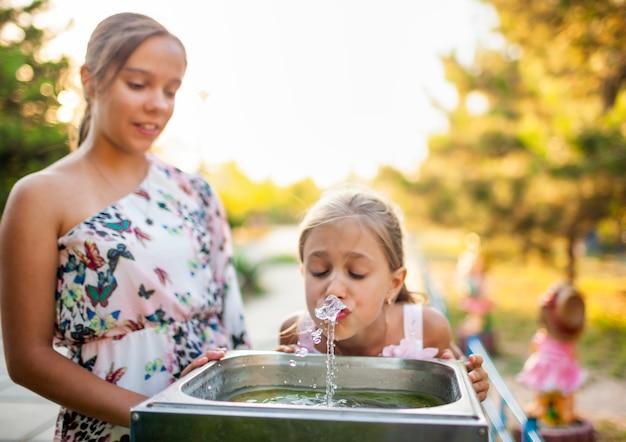 Dwie zabawne wesołe cudowne siostry piją chłodną świeżą wodę z małej fontanny w letnim ciepłym słonecznym parku na długo oczekiwane wakacje
