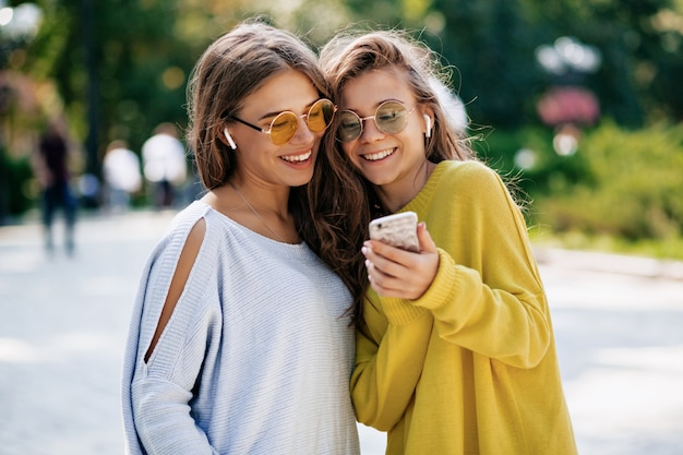 Dwie zabawnie uśmiechnięte siostry robiące selfie na smaptphone i słuchające muzyki, pozujące na ulicy, wakacyjny nastrój, szalone pozytywne uczucie, letnie jasne okulary przeciwsłoneczne.