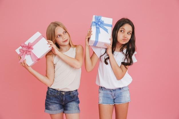 Dwie zaciekawione dziewczyny w wieku 8-10 lat w zwykłych ubraniach, trzymając i potrząsając pudełkami z kolorowymi kokardkami, odizolowane na różowym tle