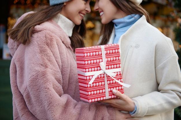 Dwie zakochane kobiety trzyma prezent na boże narodzenie