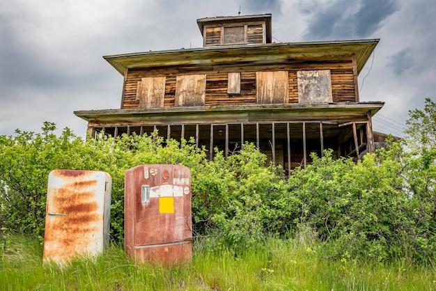 Dwie zardzewiałe lodówki vintage porzucone przed starym domem na prerii