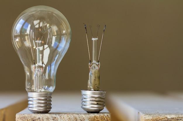 Dwie żarówki elektryczne, jedna dobra, a druga zepsuta. abstrakcyjny pomysł porównywania czegoś.
