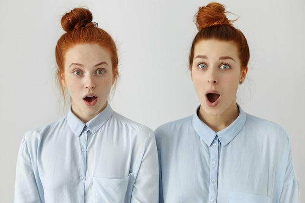 Dwie zaskoczone rudowłose pracownice w tych samych fryzurach i podobnych koszulach wyglądające w szoku, z szeroko otwartymi ustami i opuszczonymi szczękami, zdziwione plotkami o kolegach