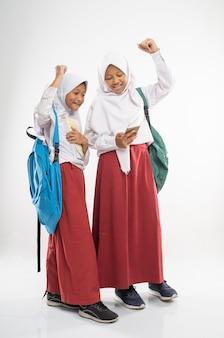 Dwie zawoalowane dziewczyny w mundurkach szkoły podstawowej, korzystające z telefonu komórkowego wraz z plecakiem