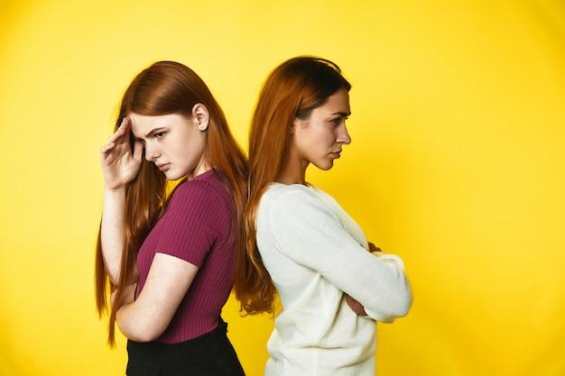 Dwie zdenerwowane rudowłosy dziewczynki stoją rozczarowane plecami do siebie ubrane w zwykłe ubrania