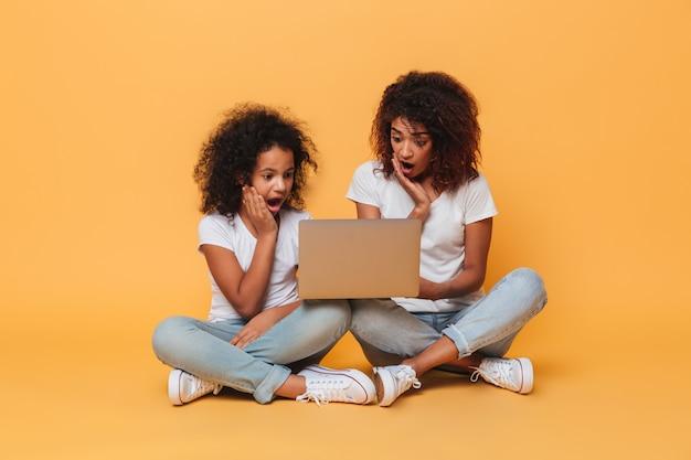 Dwie zdziwione afro amerykańskie siostry używa laptopu
